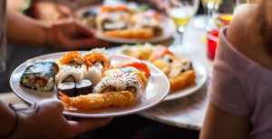 customers being served sushi at japanese restaurant